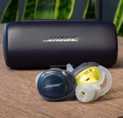 Bose SoundSport Free headphones for running on a wooden surface next to their case