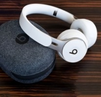 Beats Solo Pro on-ear headphones with their case on a wooden surface