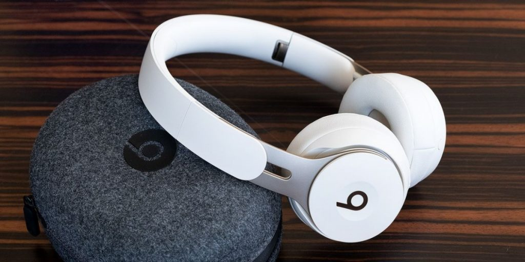 Beats Solo Pro headphones with their case on a wooden surface