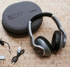 AKG N700NC over-ear headphones with their case and some wires on a wooden surface