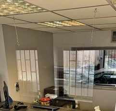 Plastic Solutions Hanging Sneeze Guard hanging from the ceiling