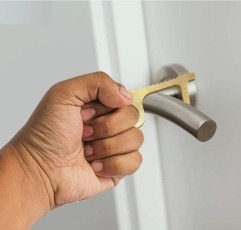 Tanness no touch tool being used to open a door