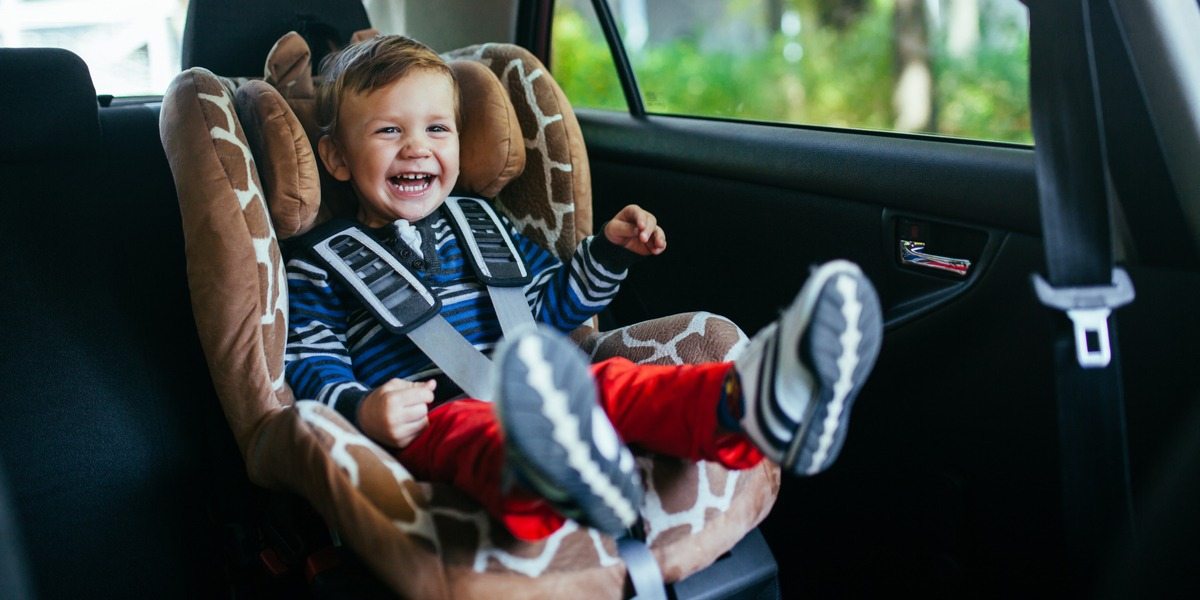 A kid sitting in a car seat laughing