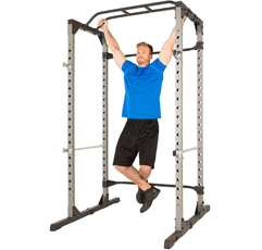 Fitness Reality Squat Rack with a man hanging to work out his upper arm muscles