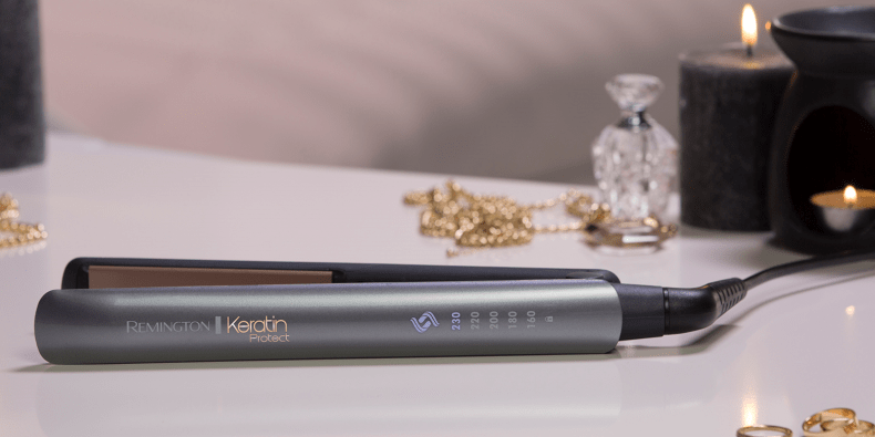 Remington Keratin Protect Hair Straightener next to some candles and jewelry
