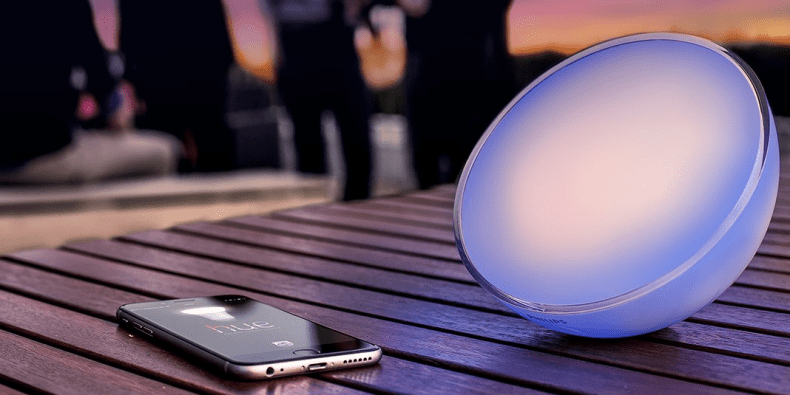 Philips Hue Go 2.0 portable light on a wooden table next to a smartphone