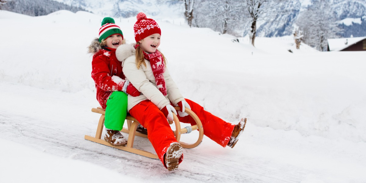 Two kids having fun on a snow sled