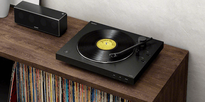 Sony PS-LX310BT Bluetooth Turntable For Vinyls on a furniture next to a speaker