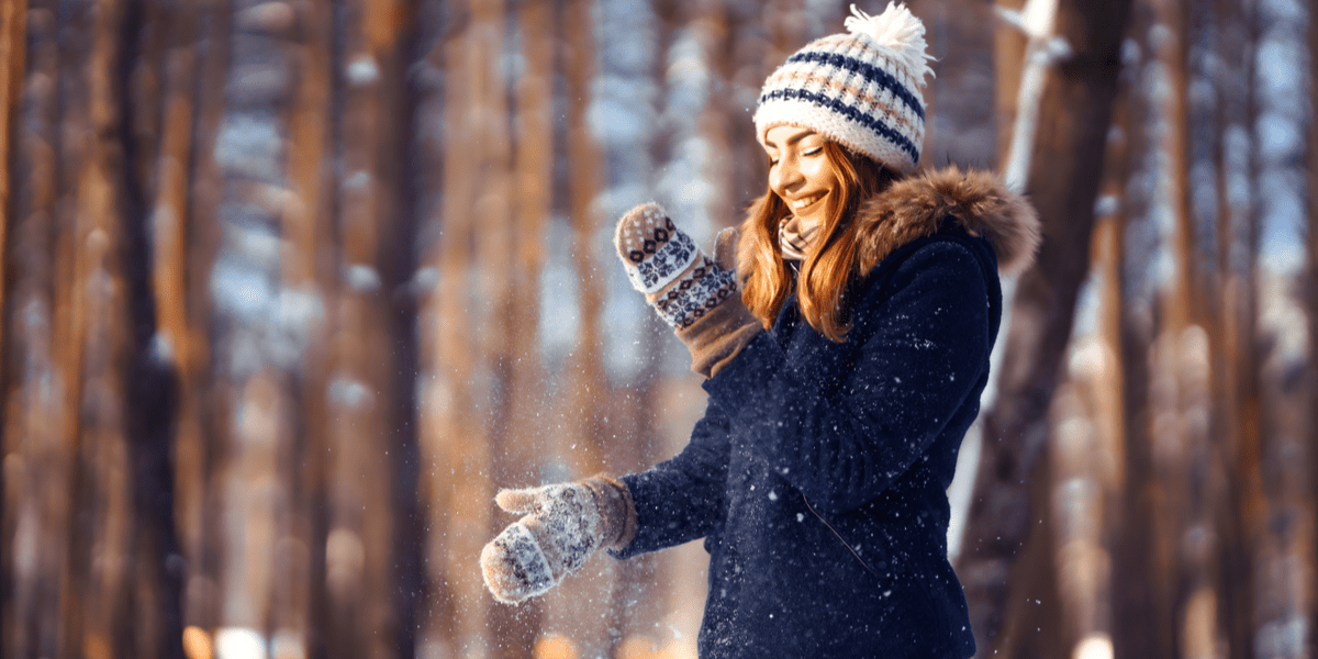 woman playing with snow wearing knitted gloves