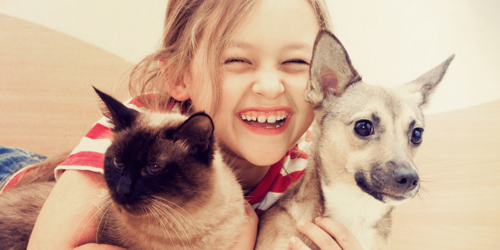 A happy little girl hugging her pets