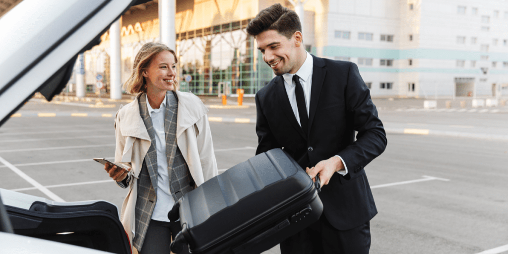 happy man and woman placing their luggage in their car in the airport parking