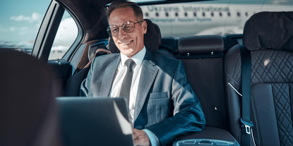 smiling businessman working on his laptop being picked up with an airport transfer service from the airport