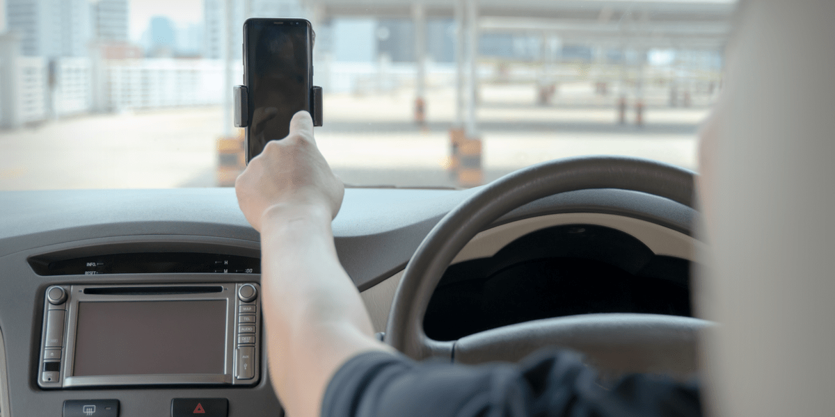 man answering a call while driving from his phone that's placed on a car phone holder