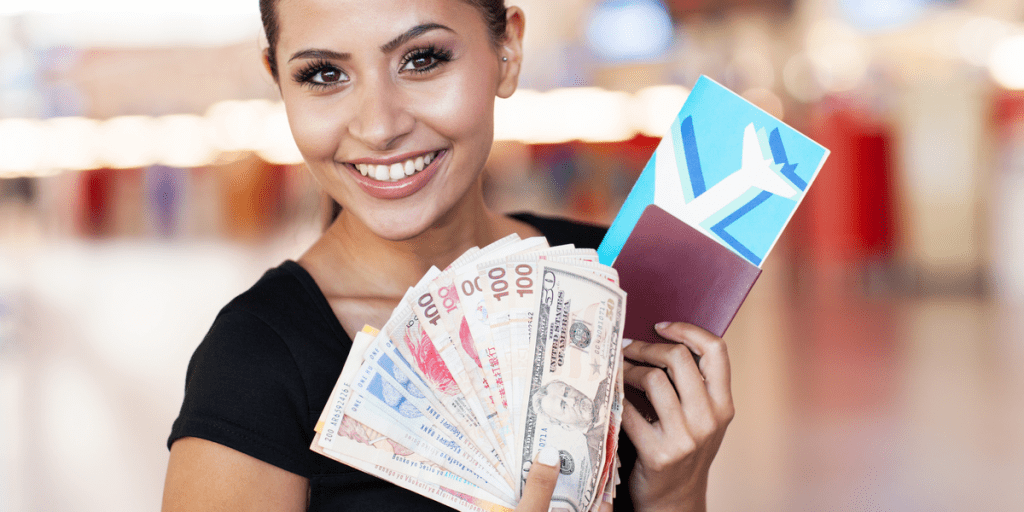 happy woman holding different international currencies and her passport and boarding pass at the airport