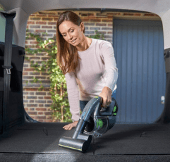 woman using the Gtech Handheld Vacuum Cleaner in her car boot