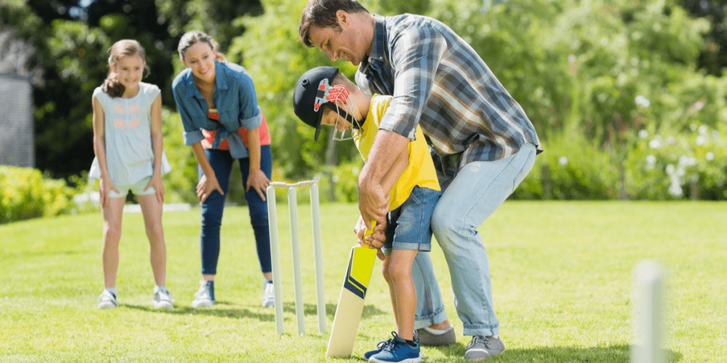 happy family playing outside while dad and son practise how to hit with a cricket bat