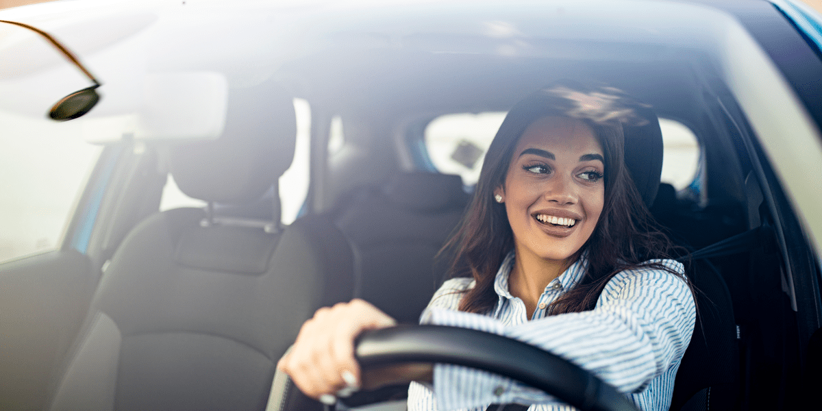 smiling woman driving her car while sitting comfortably on the car seat covers