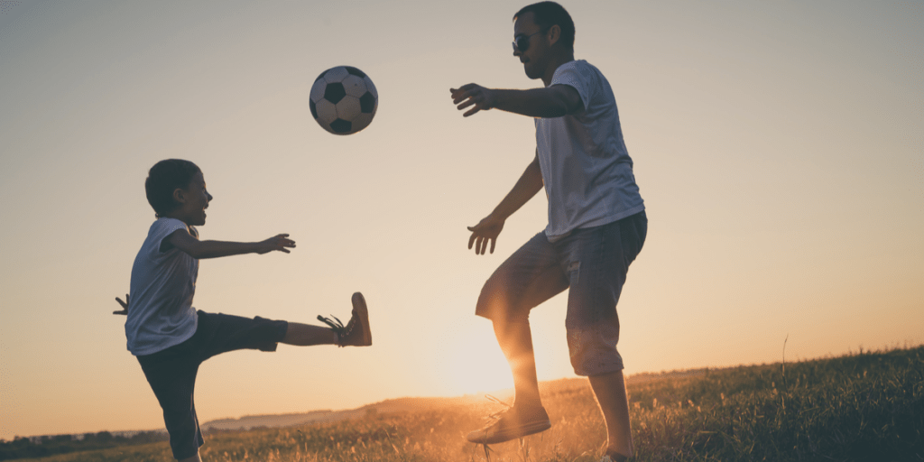 father and son playing football with a football ball at the sunset