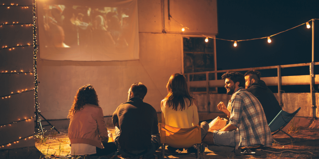 a group of friends watching a movie using the best outdoor projector screen and having a good time