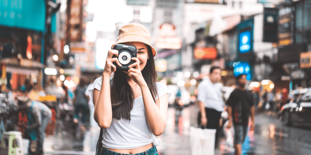 smiling young woman taking photos with an instant film camera on the streets of Thailand