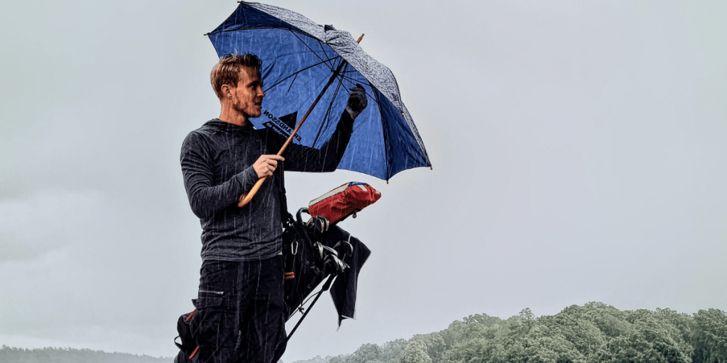 pouring rain on golf court and man is opening up his golf umbrella