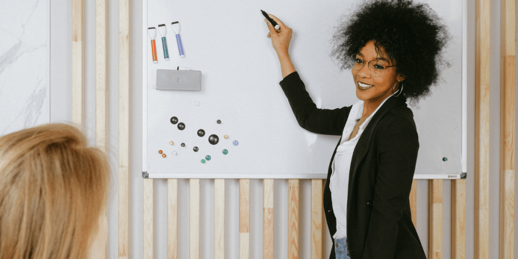 smiling woman at work uses the best magnetic whiteboards for a presentation