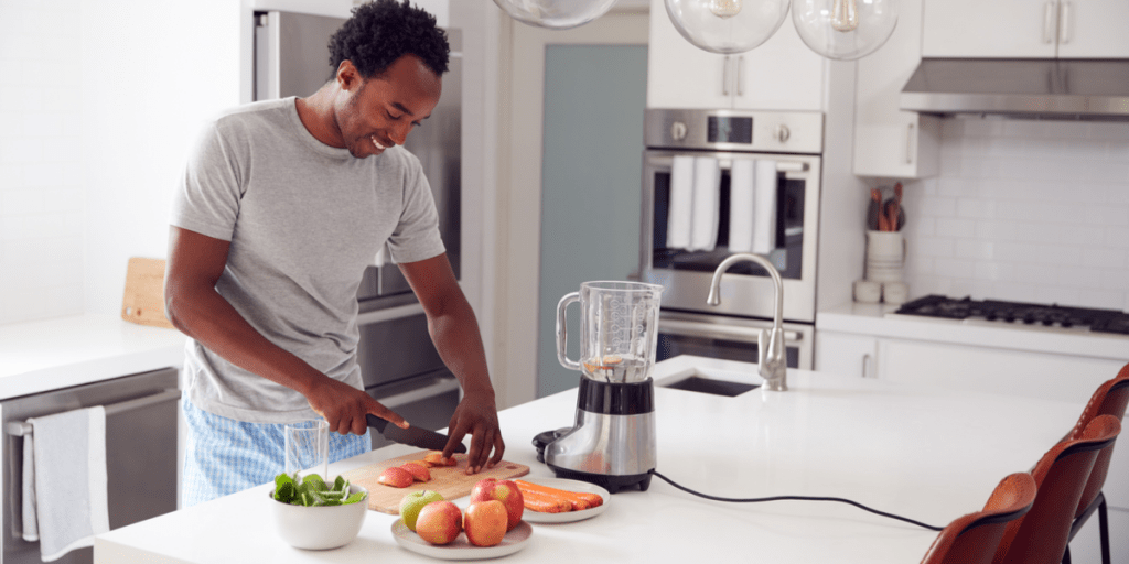 smiling man chopping vegetables in his kitchen wearing one of the best men's pyjama sets